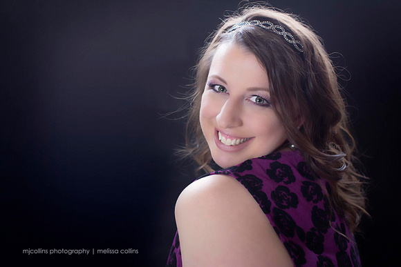 Young woman looking over her shoulder smiling inside a studio with natural light and studio light